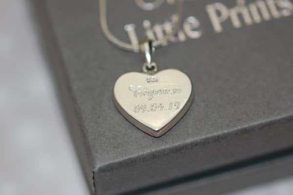 Pet name and date engraved on the back of silver heart pendant with pet fur or cremation ashes
