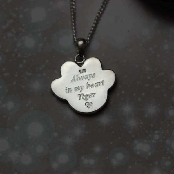 Pet name and message engraved on silver paw print pendant with pet fur or cremation ashes