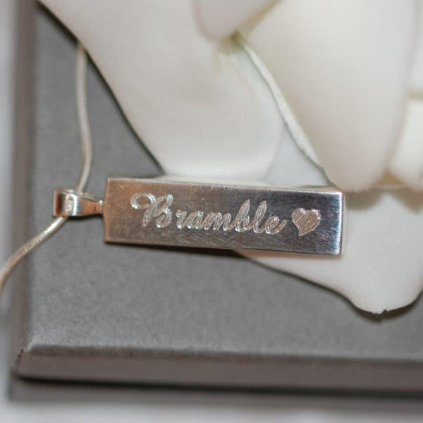 Pet name and heart engraved on the back of silver rectangle pendant with pet fur or cremation ashes