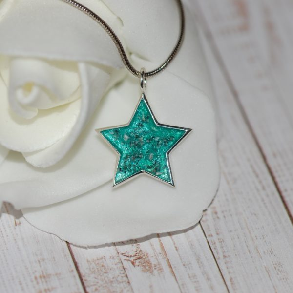 Silver star pendant with pet cremation ashes and teal colour