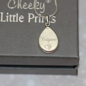 Pet name inscribed on the back of a silver tear drop pendant with pet fur or cremation ashes