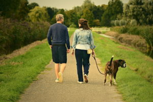 man and lady walking a dog