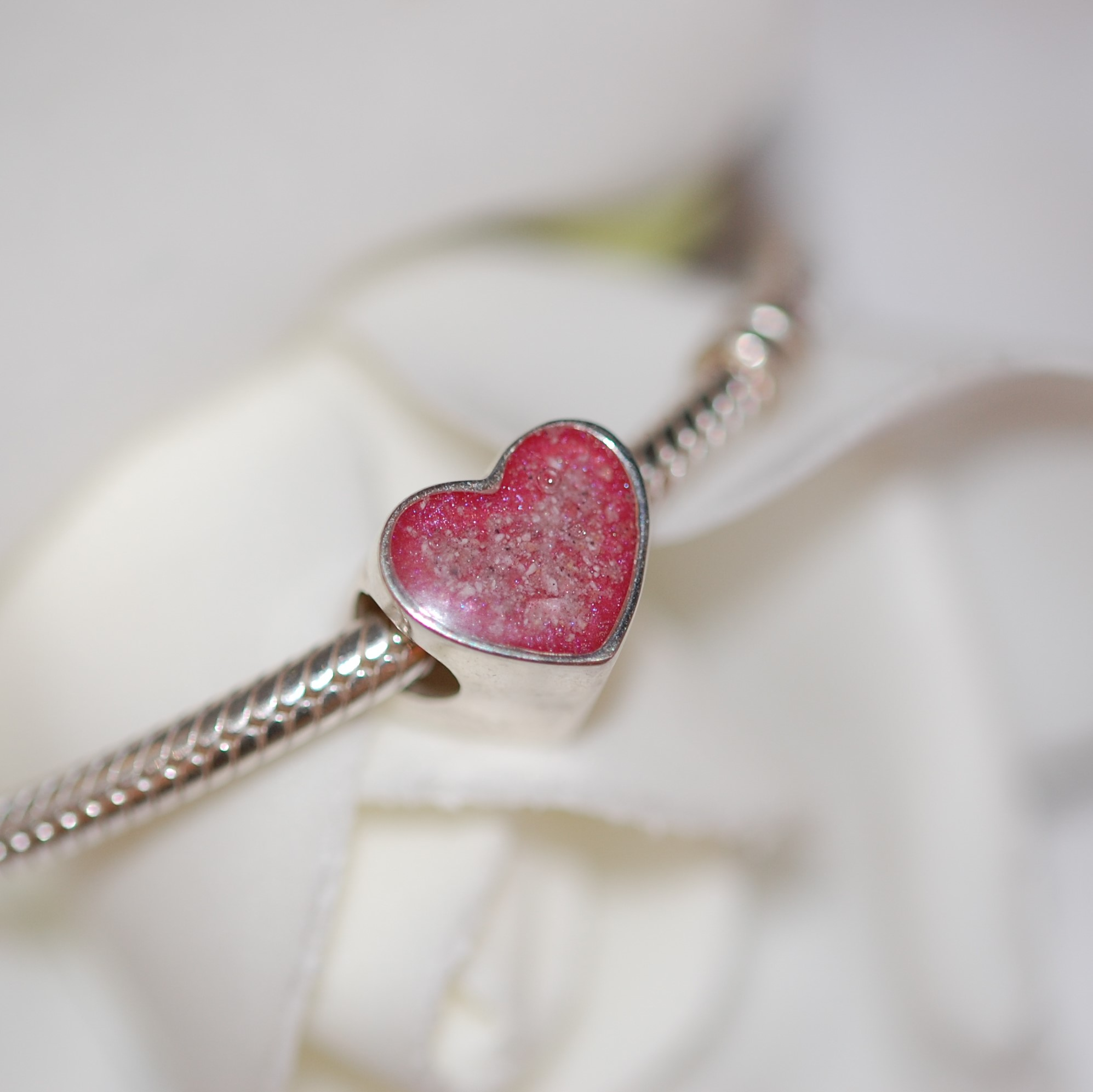 Sterling silver heart charm bead encasing pet cremation ashes in resin