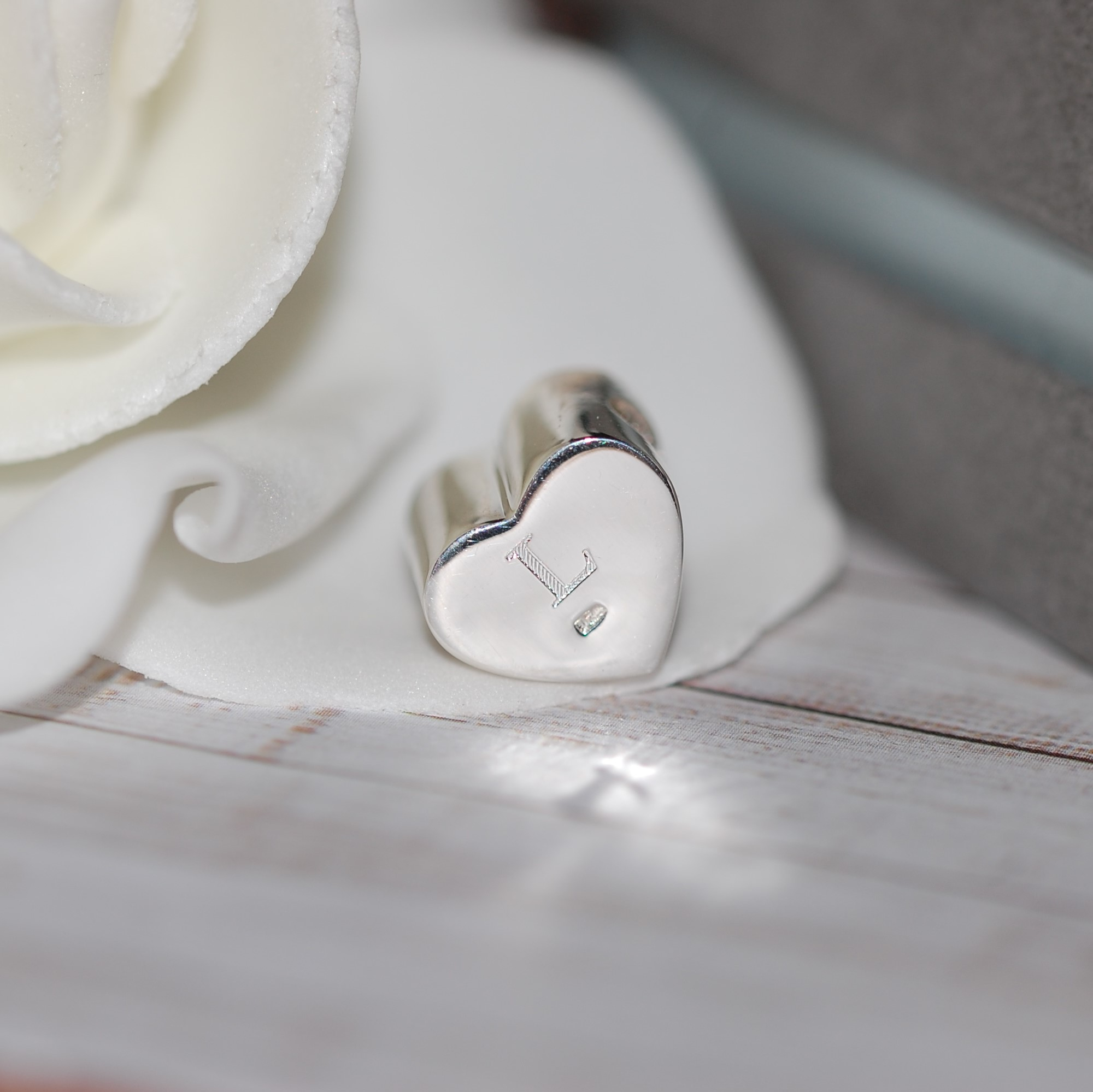 The letter L engraved on the back of sterling silver charm bead with cremation ashes