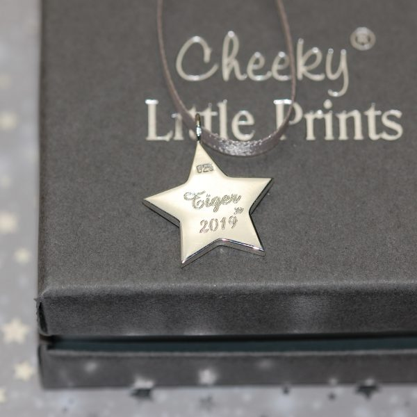 Pet name engraved on the back of sterling silver star with pet cremation ashes